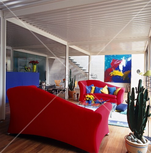 Open-plan interior with red sofas and cushions below gallery installation