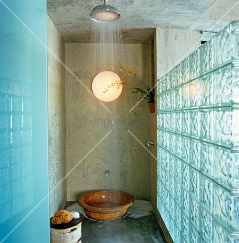 Running shower head in shower area with glass brick wall