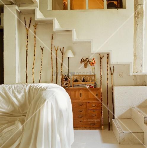 Geschnitzte Stocksammlung In Treppennische Und Teilweise Sichtbare  Polstercouch Mit Weissem Überwurf