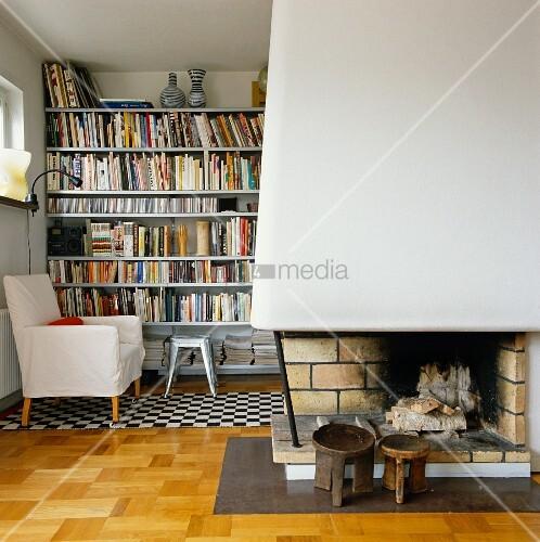 Offener Kamin und weisser Sessel vor Bücherwand im Wohnraum