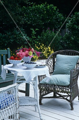 Seating area on terrace in garden with wicker chairs and set table