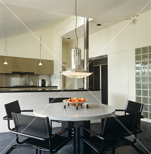Retro pendant lamp above round dining table and leather-covered cantilever chairs in front of kitchen counter