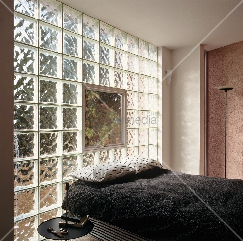 Bed with black bedspread against glass brick wall with window