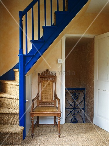 Simple stairwell with blue-painted balustrade and antique chair in niche