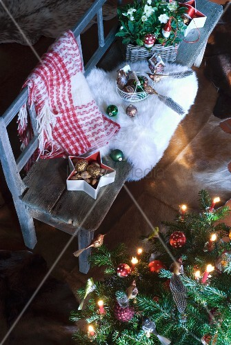 Christmas tree decorations and white fur rug on rustic bench next to decorated Christmas tree