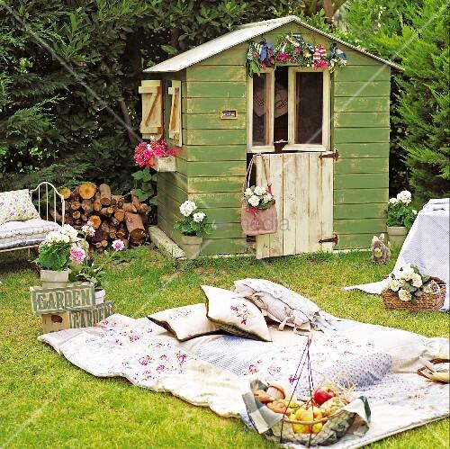 picknickidylle im garten mit patchworkdecke und vintage obstkorb vor blumengeschm cktem. Black Bedroom Furniture Sets. Home Design Ideas