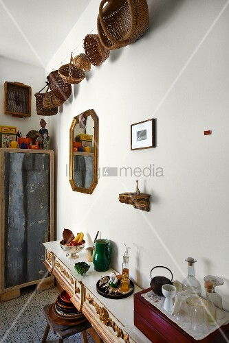 Collection of baskets on wall above hodgepodge of flea-market finds on sideboard
