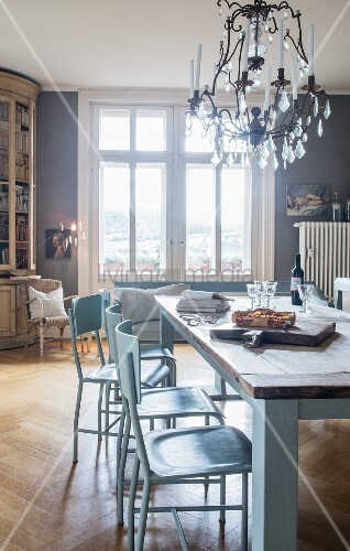 Grey-blue chairs at rustic wooden table and vintage-style chandelier in dining room
