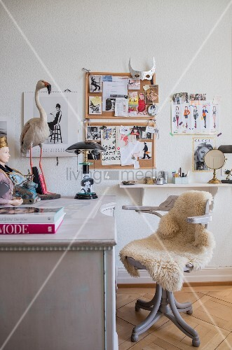 Sheepskin on antique swivel chair and stuffed flamingo on desk in front of pin boards on wall