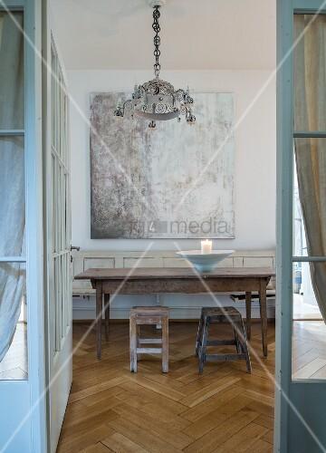 Rustic wooden table and two stools below painting seen through open door