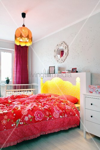 Double bed with illuminated, Oriental-style headboard and red floral bed linen