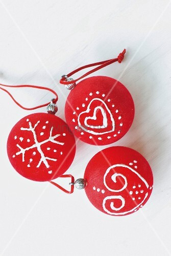 Red Christmas-tree baubles with hand-painted motifs on white surface
