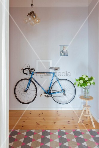 Blue bike hung on hallway wall next to flowers on stool