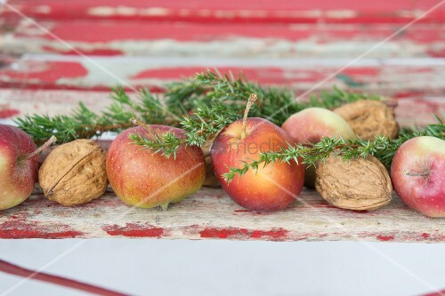 Festive arrangement of apples, walnuts and juniper sprigs