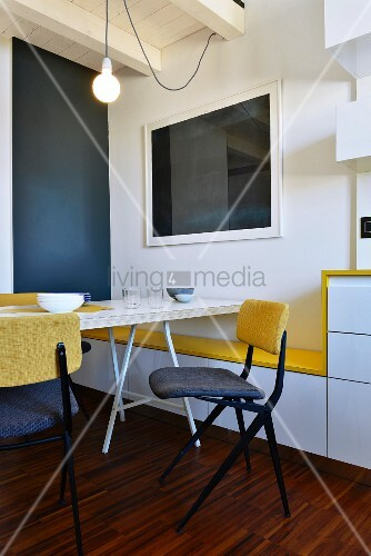 Minimalist dining chair and table next to wall with yellow seat on custom bench