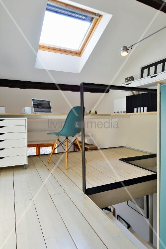 White-stained wooden floor in study area with petrol-blue classic chair below skylight on gallery