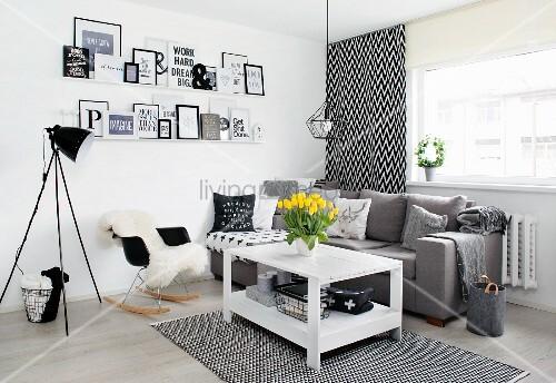 Schwarz-weisse Wohnzimmerecke mit Holztisch, grauer Polstercouch und gerahmten Botschaften