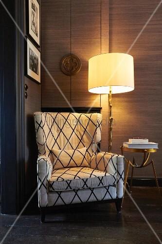 Gemütlicher Lesesessel neben beleuchteter Stehlampe und Messing-Beistelltisch