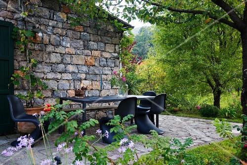 Classic black shell chairs around table on terrace of Italian farmhouse