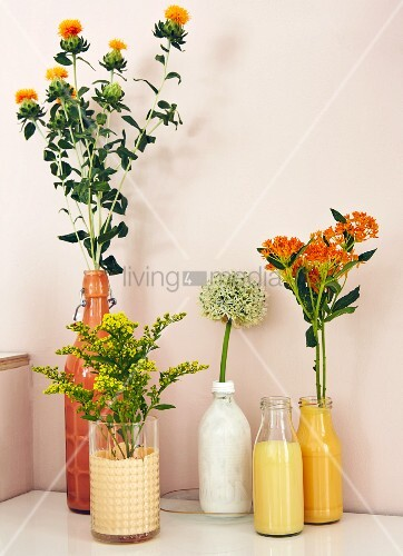 Yellow and white flowers in bottles and glasses painted matching colours