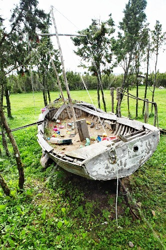 Rustic sailing dinghy on lawn used as sandpit
