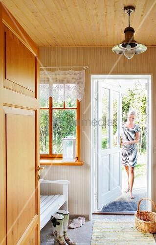 Wooden bench in hallway with lattice window and woman walking in through open exterior door