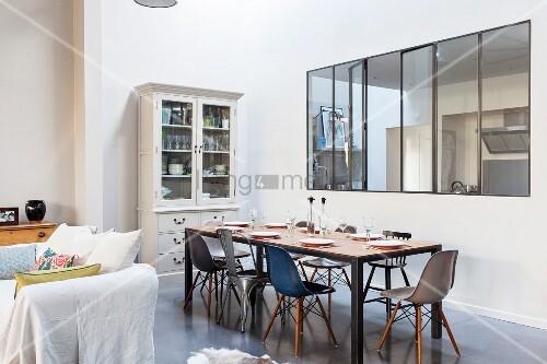 Essbereich mit Klassikerstühlen und nostalgischem Vitrinenschrank vor Innenfenster in Loft-Wohnung