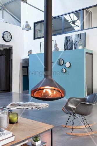 Offener Wohnbereich mit Hängekamin und Kaminfeuer in Loft-Wohnung