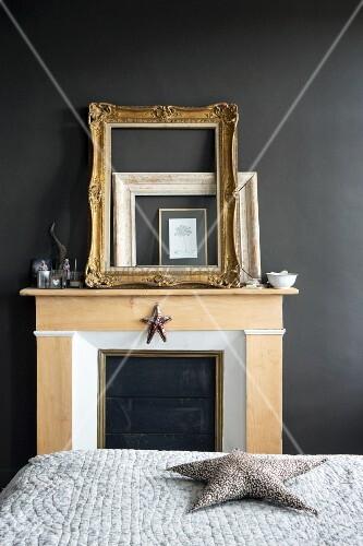 Goldrahmen an schwarze Wand gelehnt auf Kaminsims in Schlafzimmer