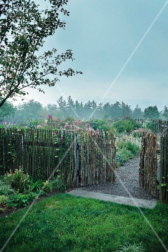 A stave fence with an open gate and a view of a garden