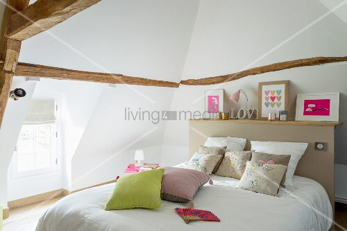 Double bed with shelf on top of beige headboard in converted attic with dormer window