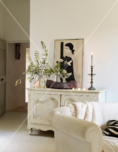 Olive branches, wooden bowl, candlestick, tealights and picture of woman on top of white vintage cabinet