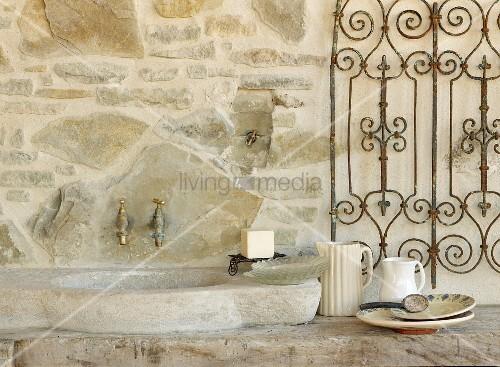 sp lbecken aus stein und wandarmaturen an natursteinwand. Black Bedroom Furniture Sets. Home Design Ideas