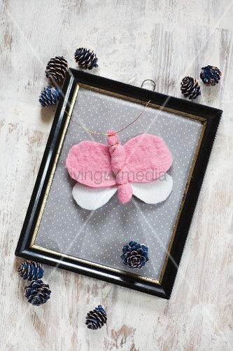Hand-made felt butterfly in vintage picture frame surrounded by pine cones