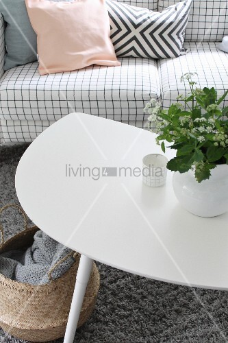 Vase of flowers on white coffee table and sofa with checked upholstery