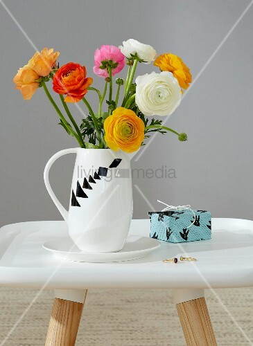 A bunch of buttercups in a white jug decorated with various tangram shapes next to a small present