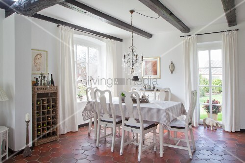 Checked tablecloth and chandelier in dining area of renovated farmhouse