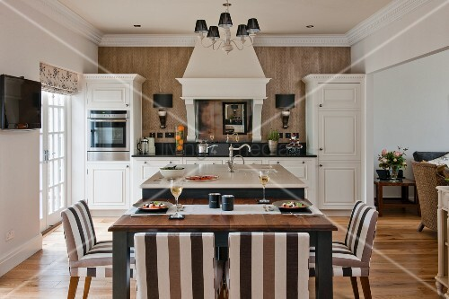 Island counter and set dining table in white, open-plan, country-house kitchen