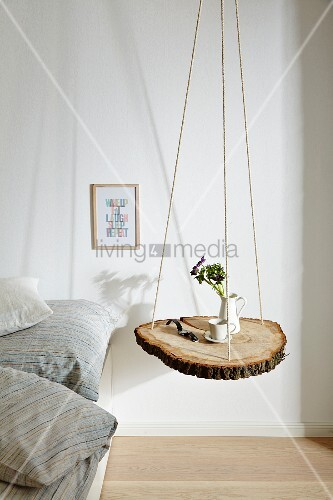 Slice of tree trunk hung from ropes and used as bedside table