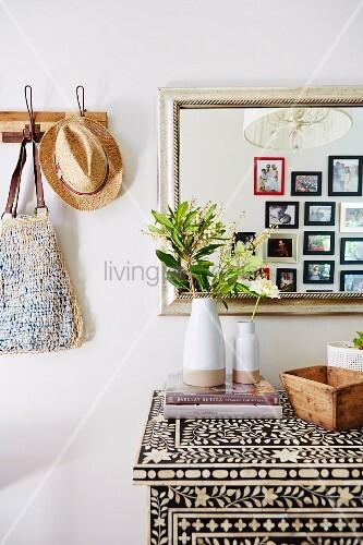 Ethno-Kommode mit Perlmutt-Intarsien, darauf Vasen mit Blütenzweigen vor Wandspiegel