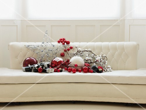 Red and silver Christmas decorations on elegant white sofa