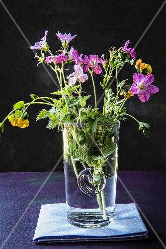 Small bunch of wild flowers in glass of water