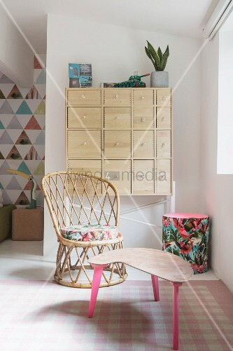 Wicker chair and upcycled side table in cosy seating area of bright bedroom