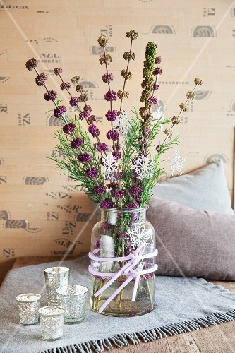 Wintry arrangement of tealight holders and branches of beautyberry in glass vase on tale