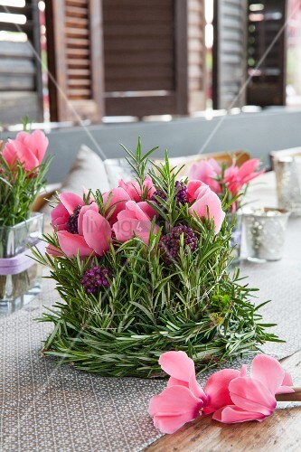 Romantic arrangement of cyclamen, beautyberrry and sprigs of rosemary