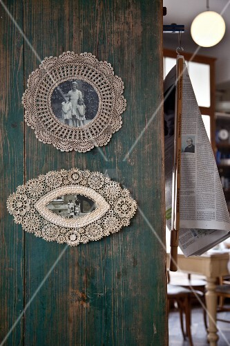Old photos framed in lace doilies on vintage wooden wall