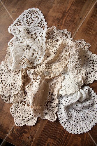 Various lace doilies on rustic wooden table