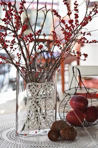 Herbstliche Tischdekoration mit Zapfen, Drahtkorb und roten Beerenzweigen in Glasvase mit Häkeldeckchen dekoriert