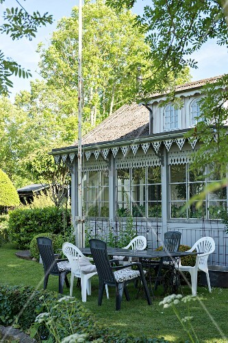 Seating area outside traditional conservatory with ornate wooden eaves and lattice windows