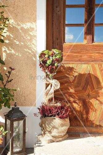 Moss heart with fruits, honesty, heather and houseleeks next to exterior door